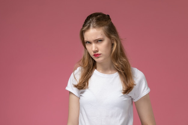Widok z przodu młoda atrakcyjna kobieta w białej koszulce pozuje z niezadowolonym wyrazem twarzy na różowej ścianie modelka pozuje kolorowe zdjęcie