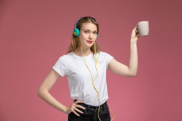 Widok z przodu młoda atrakcyjna kobieta w białej koszulce słuchanie muzyki trzymając kubek z uśmiechem na różowej ścianie kolor modelu samica młoda dziewczyna