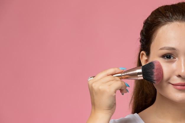 Widok z przodu młoda atrakcyjna kobieta w białej koszulce smi i robi makijaż na różowym tle