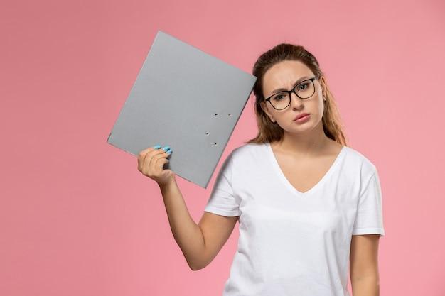 Widok z przodu młoda atrakcyjna kobieta w białej koszulce trzyma szary plik i myśli na różowym tle