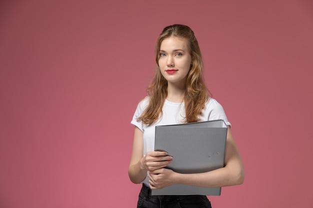 Widok z przodu młoda atrakcyjna kobieta w białej koszulce trzymając szary plik na różowej ścianie kolor modelu kobieta młoda