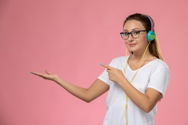 Widok z przodu młoda atrakcyjna kobieta w białej koszulce tylko pozuje i słucha muzyki przez słuchawki, uśmiechając się na różowym tle