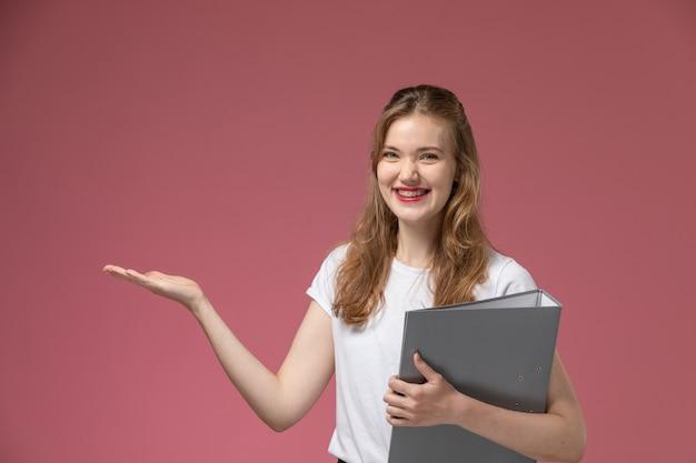 Widok z przodu młoda atrakcyjna kobieta w białej koszulce uśmiechnięta gospodarstwa szary plik na różowej ścianie kolor modelu samica młoda