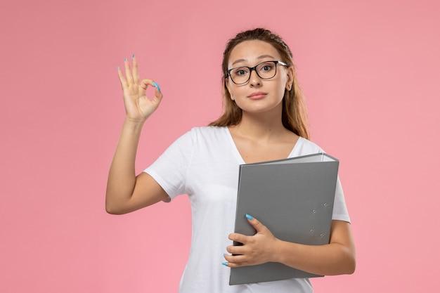 Widok z przodu młoda atrakcyjna kobieta w białej koszulce z szarym plikiem na różowym tle
