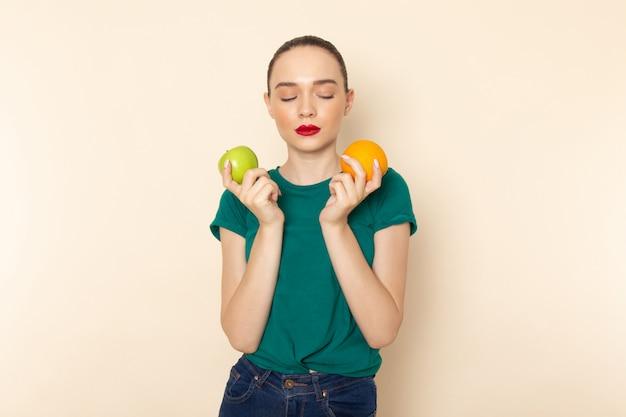 Widok z przodu młoda atrakcyjna kobieta w ciemnozielonej koszuli trzyma pomarańczę i jabłko na beżu