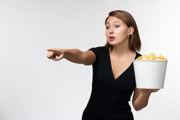 Widok z przodu młoda atrakcyjna kobieta w czarnej koszuli trzymając kipsy ziemniaczane oglądając film na białej powierzchni