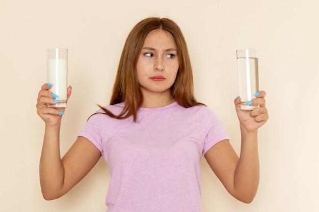 Widok z przodu młoda atrakcyjna kobieta w różowej koszulce i dżinsach trzyma mleko i wodę