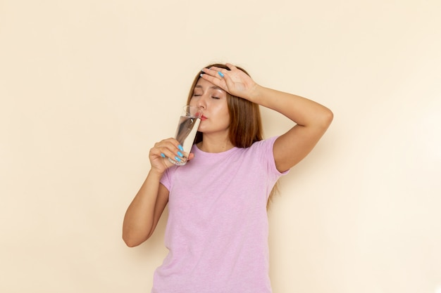 Widok z przodu młoda atrakcyjna kobieta w różowej koszulce i dżinsach wody pitnej