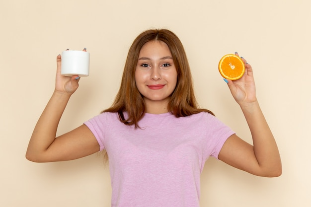 Widok z przodu młoda atrakcyjna kobieta w różowej koszulce i niebieskich dżinsach trzyma pomarańczowy