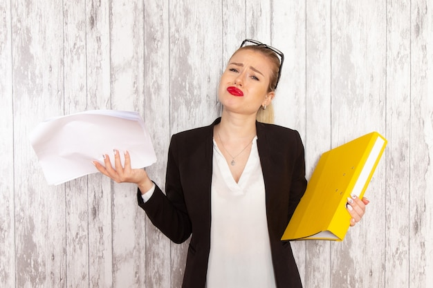 Widok z przodu młoda bizneswoman w ścisłej czarnej kurtce trzymając pliki na białym biurku