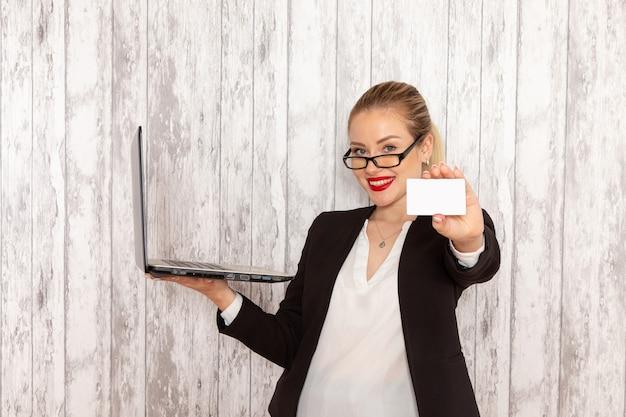 Widok z przodu młoda bizneswoman w ścisłej czarnej kurtce ubrania za pomocą swojego laptopa i trzymając kartę na białej powierzchni