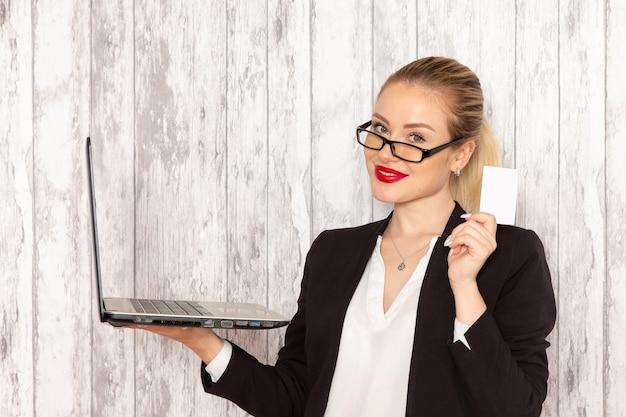 Widok z przodu młoda bizneswoman w ścisłej czarnej kurtce ubrania za pomocą swojego laptopa i trzymając kartę na białym biurku