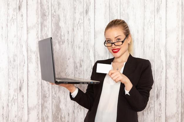 Widok z przodu młoda bizneswoman w ścisłej czarnej kurtce ubrania za pomocą swojego laptopa i trzymając kartę na jasnobiałej powierzchni