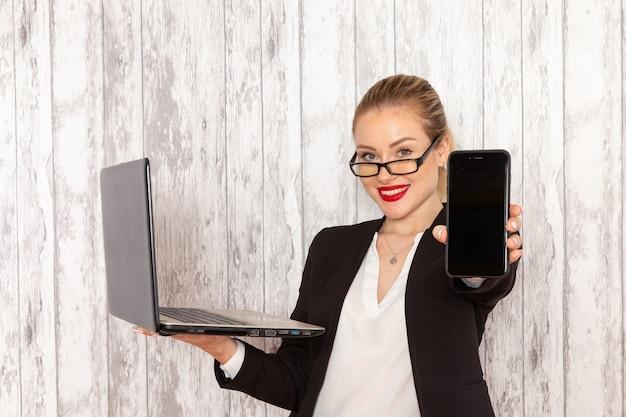 Widok z przodu młoda bizneswoman w ścisłej czarnej kurtce ubrania za pomocą swojego laptopa i trzymając telefon uśmiechnięty na białej powierzchni