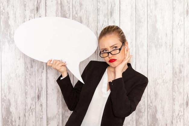 Widok z przodu młoda bizneswoman w ścisłej odzieży czarna kurtka posiadająca ogromny biały znak na białej powierzchni