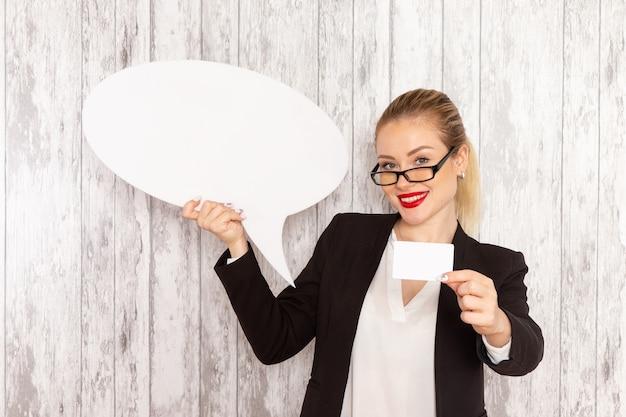 Widok z przodu młoda bizneswoman w ścisłej odzieży czarnej kurtce, posiadająca ogromny biały znak i kartę na białej powierzchni