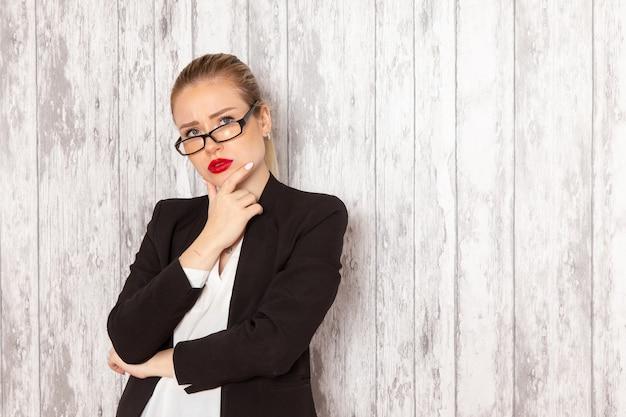 Widok z przodu młoda bizneswoman w surowych ubraniach czarna kurtka z optycznymi okularami przeciwsłonecznymi myśli na białej ścianie praca urząd pracy dama kobieta biznesu