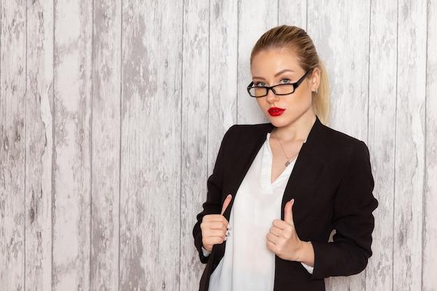 Widok z przodu młoda bizneswoman w surowych ubraniach czarna kurtka z optycznymi okularami przeciwsłonecznymi na białym biurku praca urząd kobiet spotkania biznesowe
