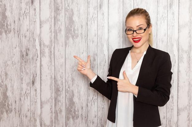 Widok z przodu młoda bizneswoman w surowych ubraniach czarna kurtka z optycznymi okularami przeciwsłonecznymi na białym biurku praca urząd kobieta spotkanie biznesowe