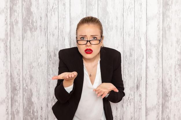 Widok z przodu młoda bizneswoman w surowych ubraniach czarna kurtka z optycznymi okularami przeciwsłonecznymi, pozowanie na białej ścianie praca biuro pracy
