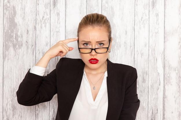 Widok z przodu młoda bizneswoman w surowych ubraniach czarna kurtka z optycznymi okularami przeciwsłonecznymi pozowanie na białej ścianie praca urząd praca dama kobieta biznesu