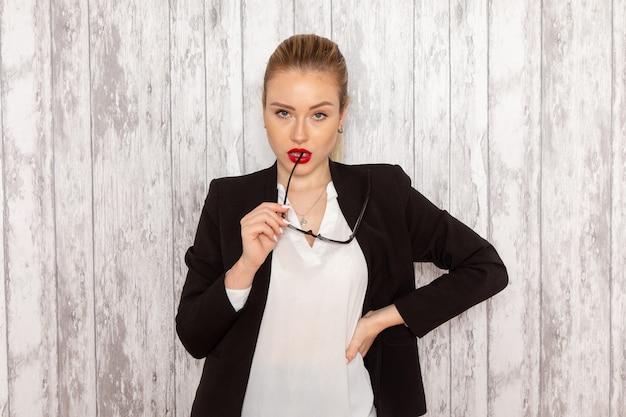 Widok z przodu młoda bizneswoman w surowych ubraniach czarna kurtka z optycznymi okularami przeciwsłonecznymi pozowanie na białej ścianie praca urząd pracy dama biznesowa