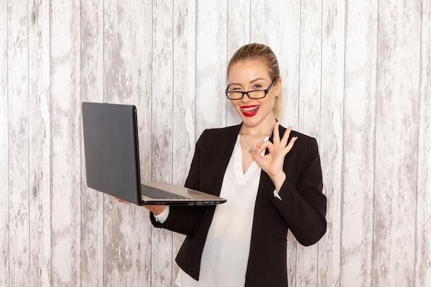 Widok z przodu młoda bizneswoman w surowych ubraniach czarna kurtka za pomocą swojego laptopa mrugając na białej ścianie urząd praca praca pracownik kobieta