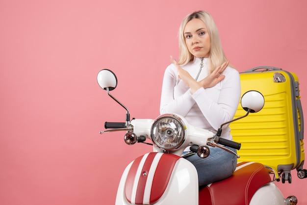 Widok z przodu młoda blondynka na skrzyżowaniu rąk motoroweru