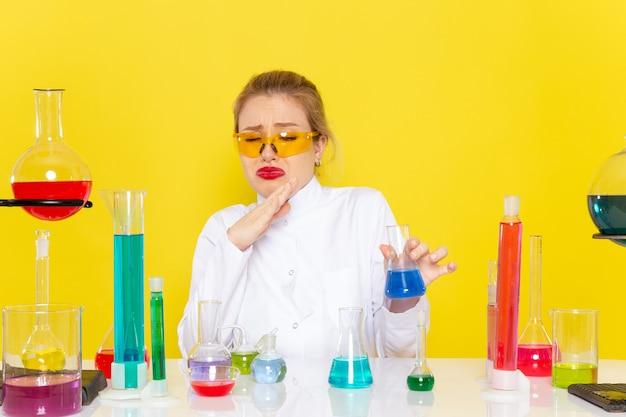 Widok z przodu młoda chemiczka w białym garniturze przed stołem z rozwiązaniami ed pracującymi z nimi na żółtym stanowisku chemii kosmicznej