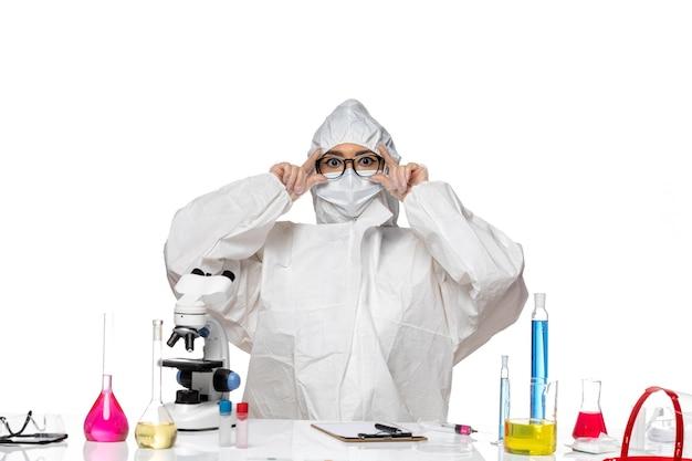 Widok z przodu młoda chemiczka w specjalnym kombinezonie ochronnym siedząca przed stołem z roztworami na białym biurku laboratorium wirusów covid zdrowie chemia