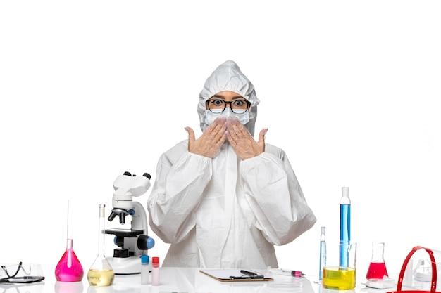 Widok z przodu młoda chemiczka w specjalnym kombinezonie ochronnym siedząca przed stołem z roztworami na białym tle laboratorium wirusów covid zdrowie chemia