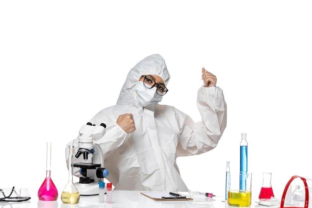 Widok z przodu młoda chemiczka w specjalnym kombinezonie ochronnym siedząca przed stołem z roztworami na jasnym białym tle laboratorium wirusów covid zdrowie chemia