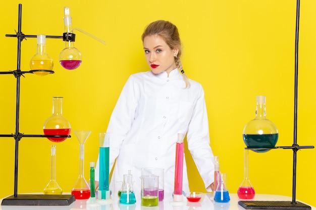 Widok z przodu młoda chemik w białym garniturze przed stołem z roztworami ed na temat eksperymentów naukowych z chemii żółtej przestrzeni
