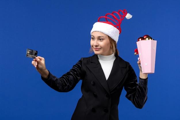 Widok z przodu młoda dama trzyma kartę bankową na niebieskiej ścianie pieniądze nowy rok emocji wakacje