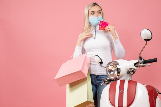 Widok z przodu młoda dama trzyma karty i kolorowe torby na zakupy w pobliżu motoroweru