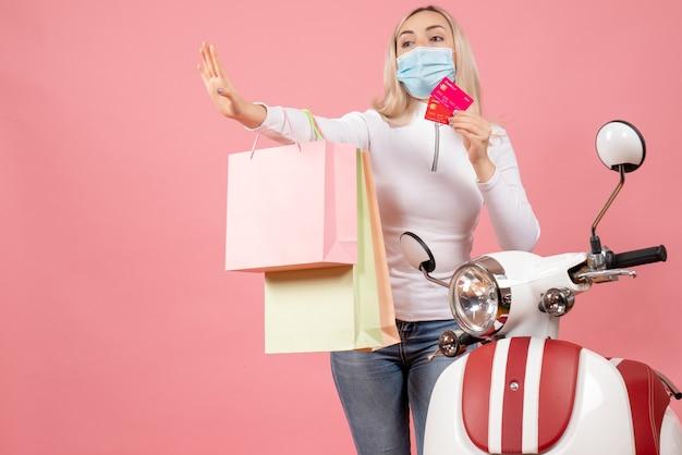 Widok z przodu młoda dama trzyma karty i torby na zakupy robi znak stopu w pobliżu motoroweru