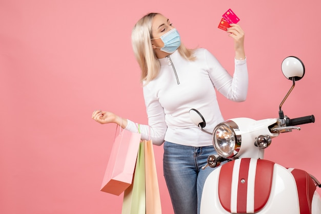 Widok z przodu młoda dama trzyma karty i torby na zakupy w pobliżu motoroweru