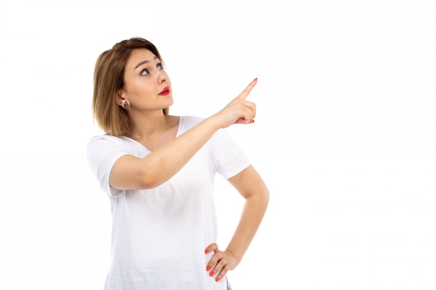 Widok z przodu młoda dama w białej koszulce, pozowanie, wskazując na niebo na białym