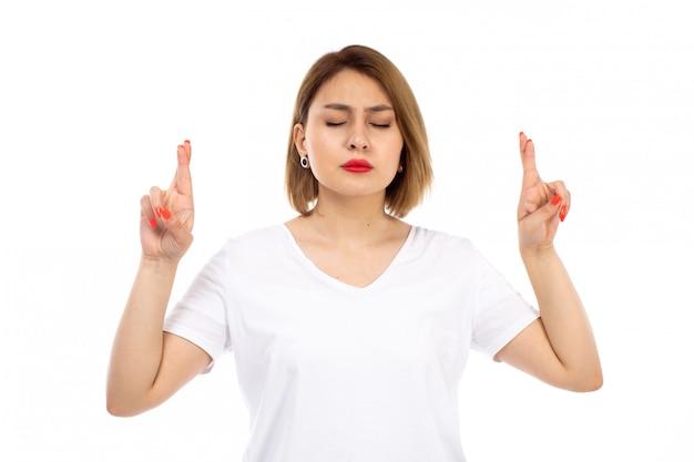 Widok z przodu młoda dama w białej koszulce pozuje skrzyżowanymi palcami z zamkniętymi oczami na białym