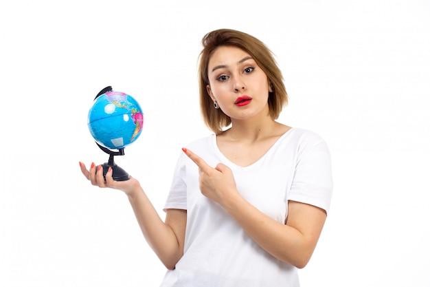 Widok z przodu młoda dama w białej koszulce trzyma małą kulę ziemską na białym
