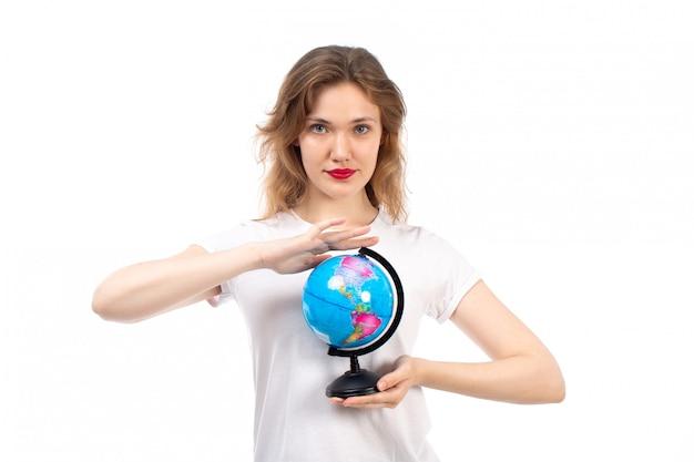 Widok z przodu młoda dama w białej koszulce trzymającej mały okrągły glob na białym