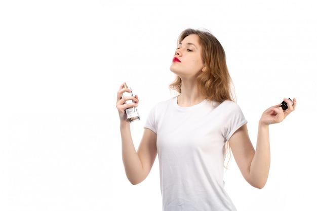 Widok z przodu młoda dama w białej koszulce, używając czarnej tubki perfum na białym tle