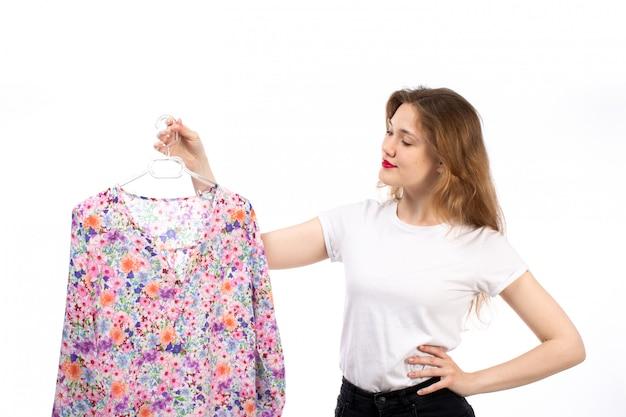 Widok z przodu młoda dama w białej koszuli i czarnych spodniach trzymająca bluzkę w kwiatki na białym tle