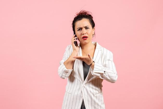 Widok z przodu młoda dama w białej kurtce rozmawia przez telefon na różowym tle moda kobieta emocje uczucie pani kolor
