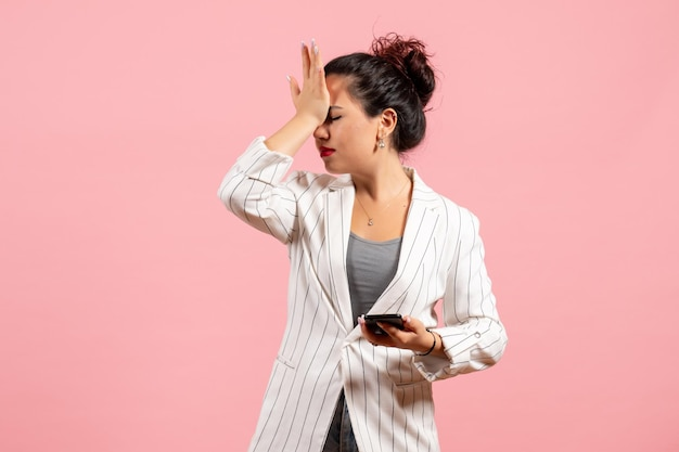 Widok z przodu młoda dama w białej kurtce trzymająca telefon na różowym tle moda kobieta emocje uczucie pani kolor