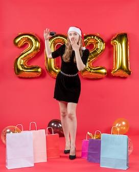 Widok z przodu młoda dama w czarnej sukience kładąca rękę na ustach torby na balonach podłogowych na czerwono
