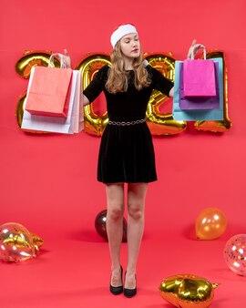 Widok z przodu młoda dama w czarnej sukience patrząca na balony torby na zakupy na czerwono