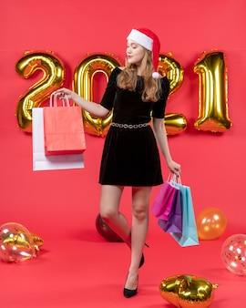 Widok z przodu młoda dama w czarnej sukience podnosząca stopę trzymająca balony z torbami na zakupy na czerwono