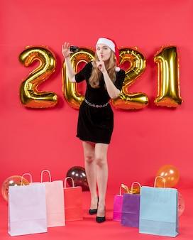 Widok z przodu młoda dama w czarnej sukience robi shh znak torby na balonach podłogowych na czerwono
