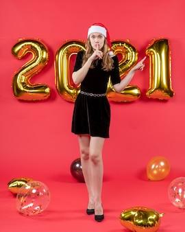 Widok z przodu młoda dama w czarnej sukience robi znak shh wskazujący na coś balonów na czerwono